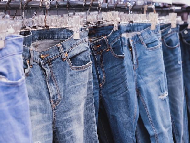 Крупным планом ряд многих синих джинсах висят