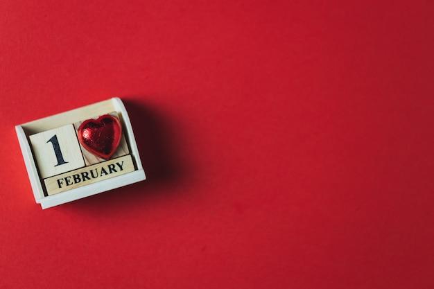 木製のブロックカレンダーと赤い背景、バレンタインのテーマ