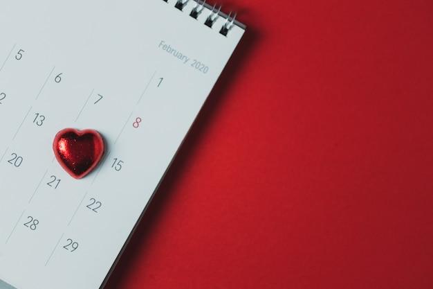 赤い背景の上に配置されたホワイトペーパーカレンダー、トップビュー、コピースペース、バレンタインテーマ