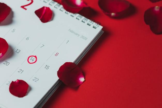 ホワイトペーパーカレンダーと赤いバラの花びらを赤いテーブル、上面図、コピースペース、バレンタインテーマに配置