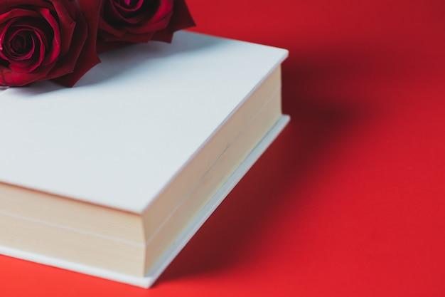 赤いバラホワイトブックに配置赤いテーブル、コンセプト、バレンタインデーのテーマ