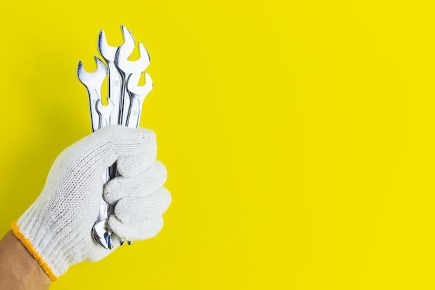 Закройте левую руку, надев белые механические перчатки, держа много гаечных ключей, желтый фон