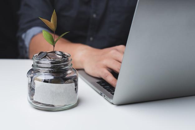 Крупным планом в стеклянной банке есть монеты внутри, и мужчины используют ноутбуки