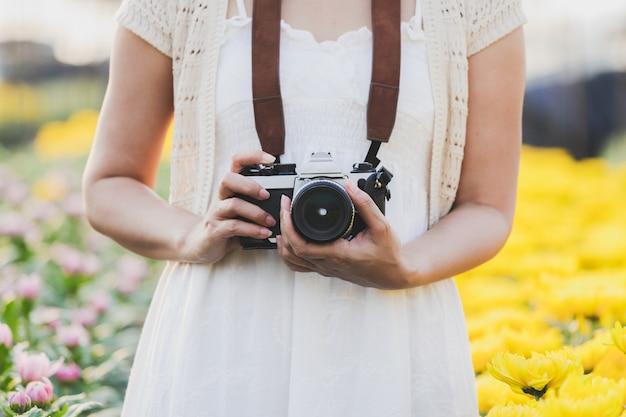 菊の庭でカメラを持って白いドレスを着ている女性