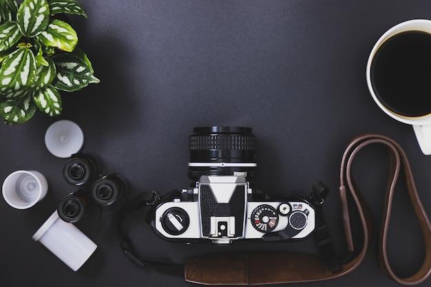 ビンテージフィルムカメラとフィルムロール、ブラックコーヒー、黒い背景に配置された木