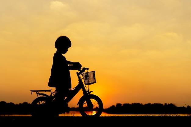 小さな女の子ライディングバイク、アジアの子供、シルエットは、夕日に子供