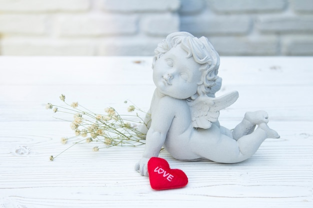 白いレンガの背景にキューピッド石メッセージバレンタイン赤いハートが大好き