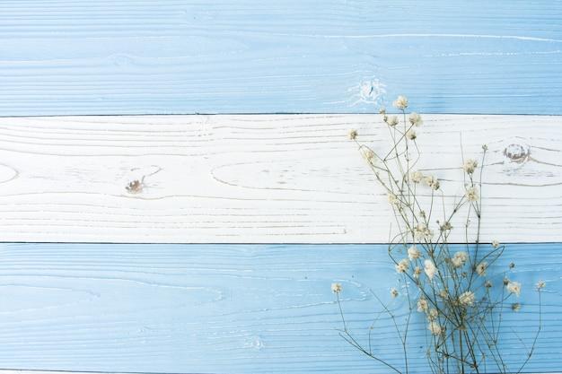 ドライフラワーで飾られたカラフルな木製の背景の平面図フラットレイアウト