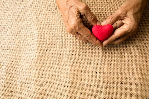 Плоские лежалые руки старухи держат красное сердце за заботу о любви с копией пространства