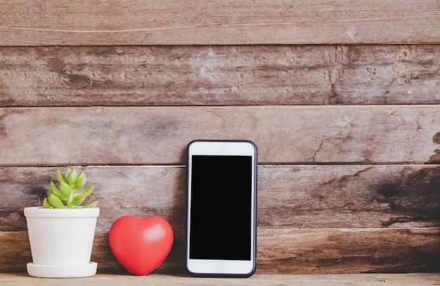 素朴な木製の背景にモックアップのスマートフォンで美しいバレンタイン赤いハートを閉じる