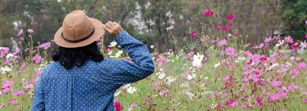 Женщина или садовник стоят перед красивым мягким селективным фокусом розового цвета