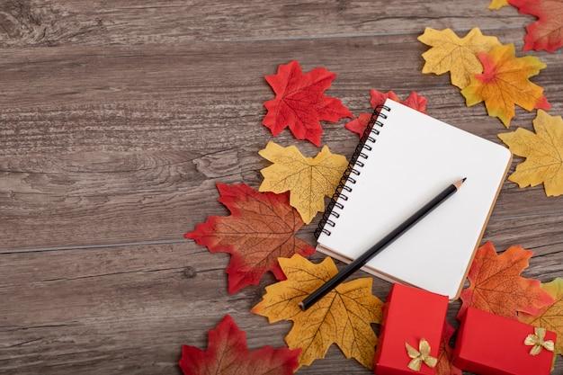 鉛筆、ギフト用の箱、メモ用紙、カエデの葉の上から見たカラフルな秋の装飾