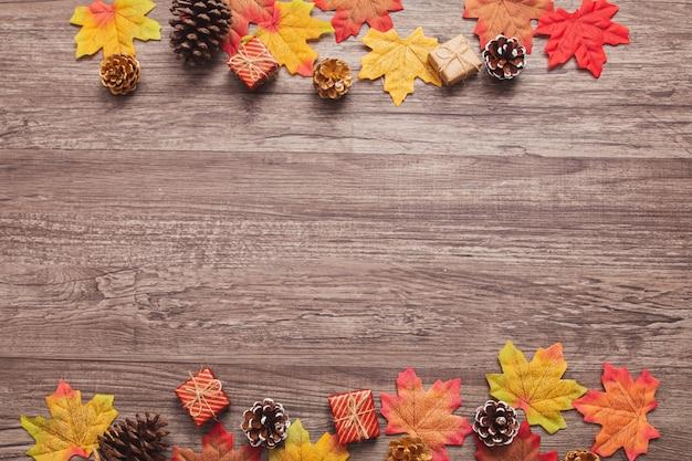 トップビューフラットレイアウト秋コンセプト、カラフルなカエデの葉、および木製の表面に乾燥したマツ円錐形