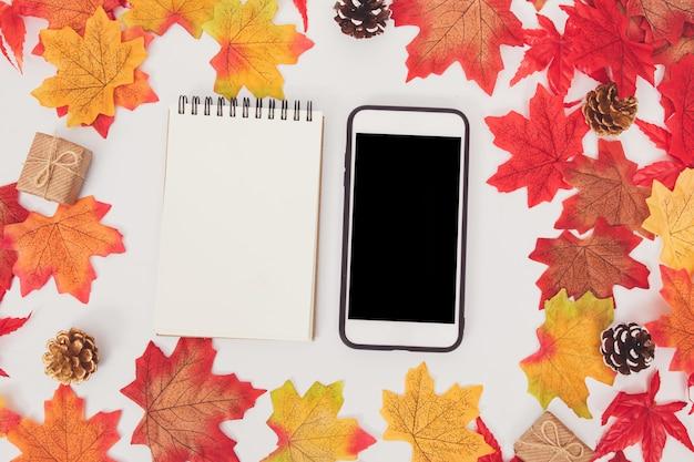 白地にカラフルなカエデで飾られたトップビューのスマートフォンとペーパーノート