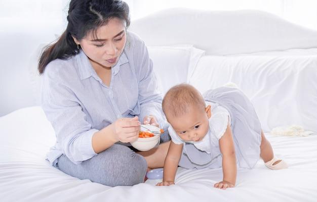 母はベッドで彼女の幼児の女の子に果物を供給