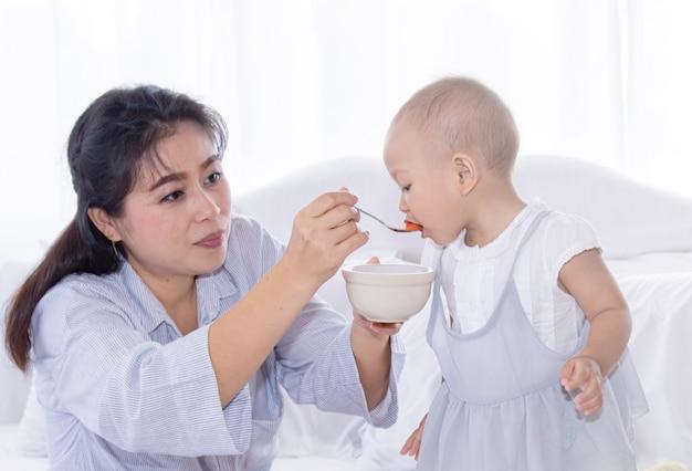 Мать кормит фрукты своей малышке в постели