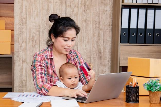 Женщина заботится о своем ребенке во время работы в офисе