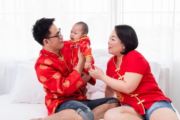 Азиатский отец, мать держат сына, малыша, мальчика на кровати у себя дома с любовью, новая китайская семья в красном китайском костюме дарит конверт ребенку, счастливой, богатой, китайской семье в китайском новогоднем празднике