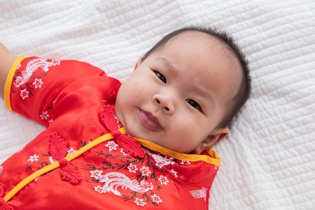 アジアのかわいい赤ちゃん男の子中国のチャイナチャイナコスチューム幼児が自宅のベッドに横になって笑って笑って良い滑稽な、幼児中国の好奇心の男の子の子供が何か、幸せな中国の新年のコンセプトを探して