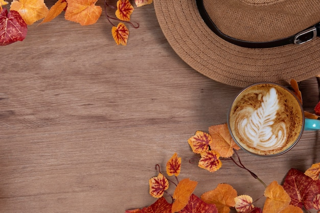 机の上にコーヒーカップと秋のファッションコンセプト