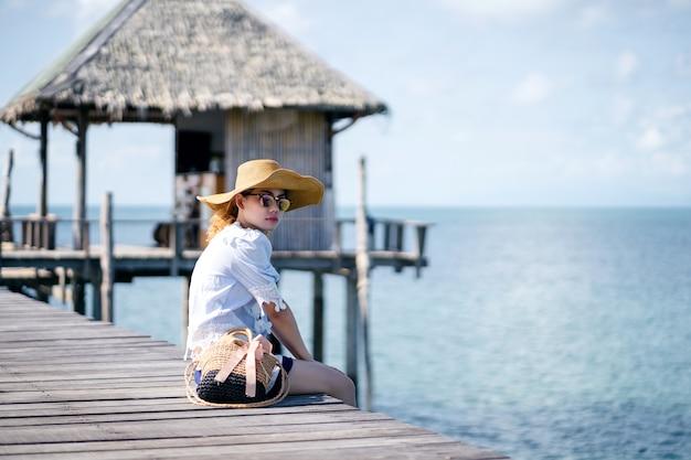 木製の橋の上に座っている一人の女性-マーク島、タイ