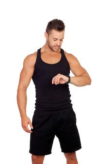 彼の時計を見てハンサムなスポーツマン