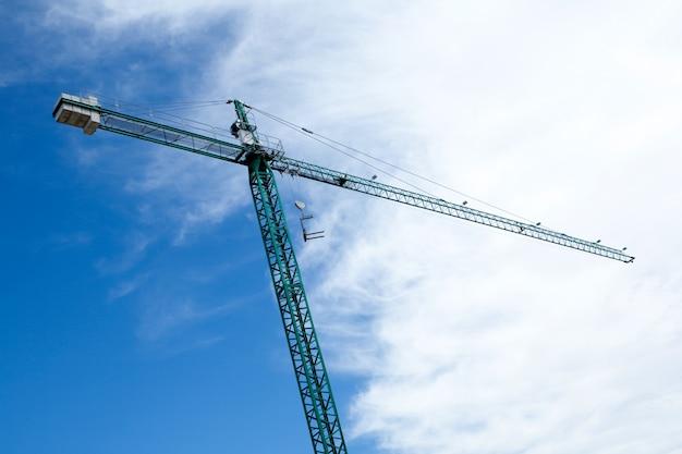 Огромный строительный кран с облачным фоном неба