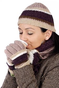 魅力的な女性は、茶色のカップを飲む冬のために守った白い背景