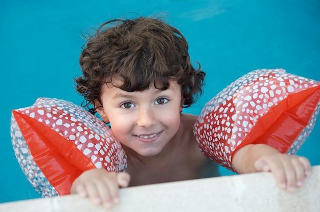 泳げることを学ぶ愛らしい少年の写真