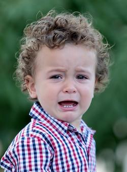 Грустный ребенок с вьющимися волосами плачет