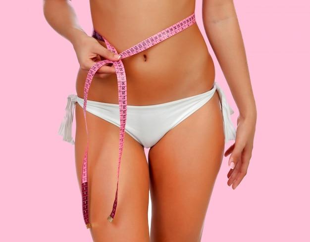 美しい体の女性が彼女の体を測定