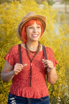 赤いシャツと自然の上を歩いてバックパックと魅力的な女性