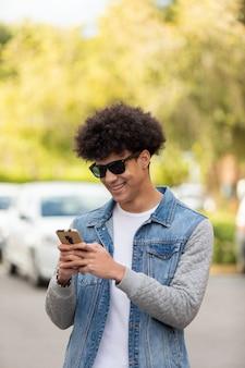 Красивый парень смотрит на мобильный