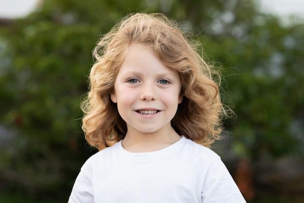 屋外の長い髪の金髪の子供