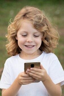 Забавный ребенок с длинными волосами держит мобильный телефон
