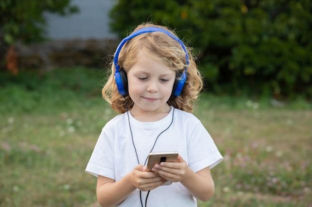 Забавный ребенок с длинными волосами слушает музыку с голубыми телефонами и мобильным телефоном
