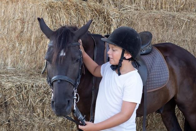 Подросток учится кататься в школе верховой езды