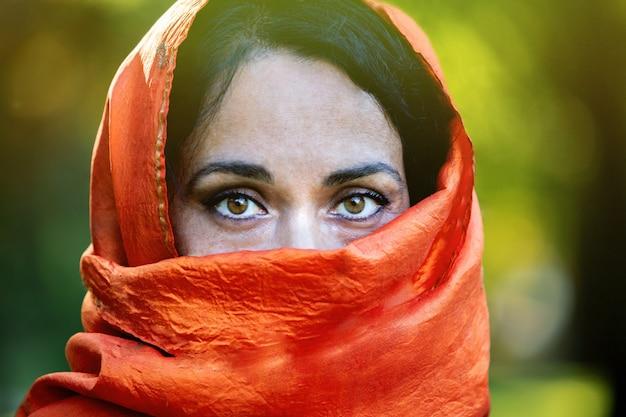 Красивая девушка с оранжевым шарфом в парке