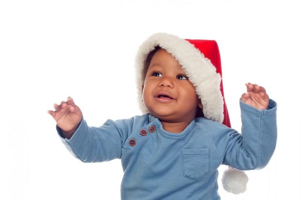 Забавный африканский ребенок с рождественской шляпой