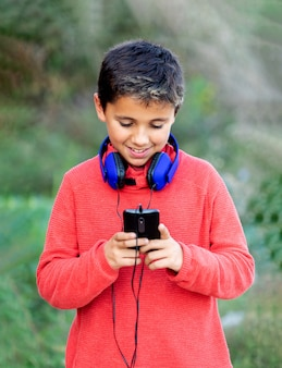 青いハドフォンと携帯電話で音楽を聴く黒髪の子