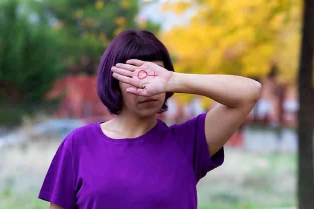 彼女の手に描かれた女性のシンボルを持つ女性