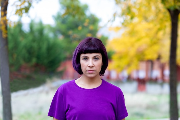Женщина в пурпуре с желтым деревом предпосылки.