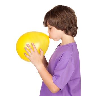 白い背景にある黄色の風船を吹くおかしい少年