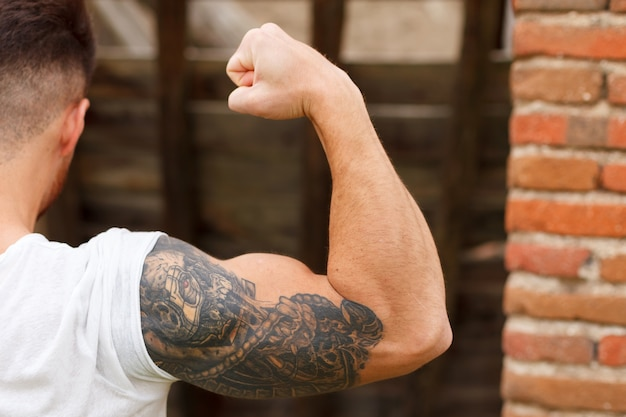 彼の腕の上に入れ墨が付いている強い男