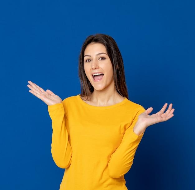 水色の壁を身振りで示すブルネットの若い女性