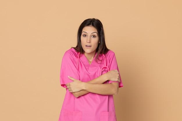 Молодая женщина-врач с розовой форме, указывая на коричневую стену