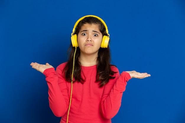 青い壁に身振りで示す赤いジャージと愛らしいプレティーンの女の子
