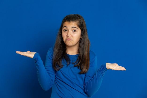 青い壁に身振りで示す青いジャージと愛らしいプレティーンの女の子