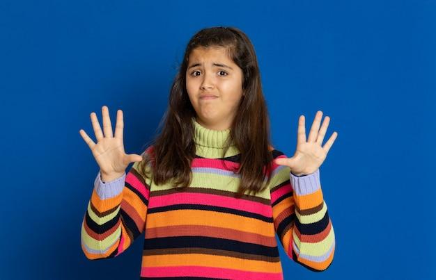 青い壁に身振りで示すストライプのジャージとプレティーンの女の子