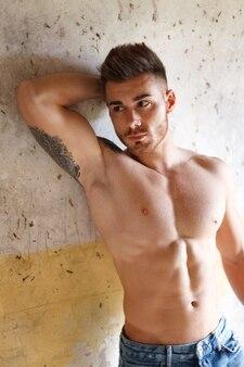 魅力的な男の彼の筋肉を示す